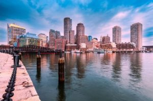 Photo of Boston's Waterfront with seawall and skyscrapers in the background.